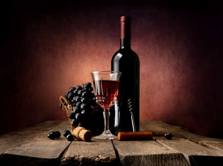 Grape in basket with wine on a wooden table Archivio Fotografico