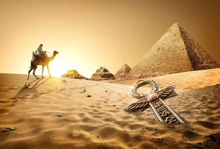 religions: Bedouin on camel near pyramids and ankh in desert
