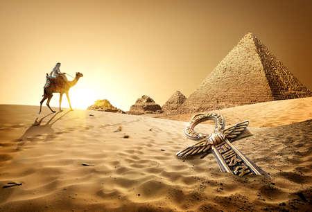 Beduino en camello cerca de las pirámides y ankh en el desierto