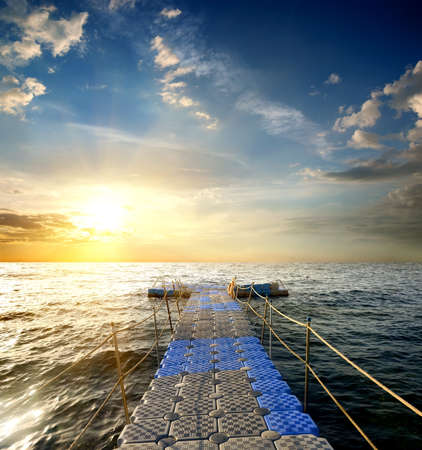 sunny: Pontoon with handrails in the sea at sunset Stock Photo