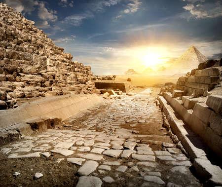 Way through ruins of egyptian pyramids and sun