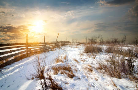 rime frost: Wooden fence in winter field at sunset