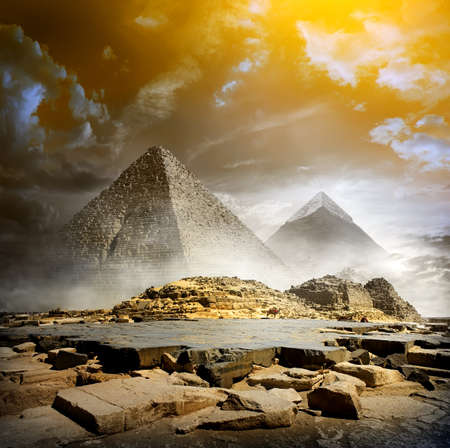 Orange storm clouds and fog over egyptian pyramids