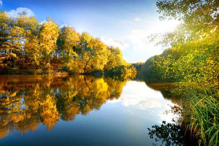 De kleurrijke herfst op kalme rivier in zonnige ochtend Stockfoto