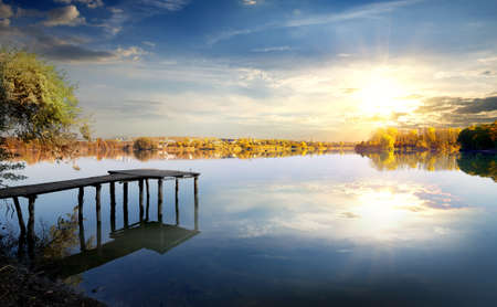 mere: Wooden pier on autumn river at sunrise Stock Photo