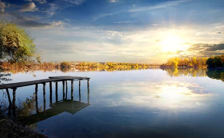 fishing pier: Wooden pier on autumn river at sunrise Stock Photo