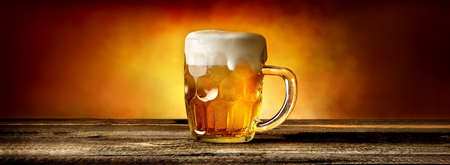 Light beer in glass mug on wooden table Stock Photo