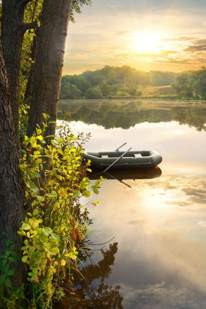 inflatable boat: Inflatable boat on river at the sunrise