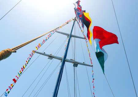 different countries: Flags of different countries on the mast of sailboat Stock Photo