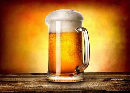 Beer in mug on wooden table and yellow background