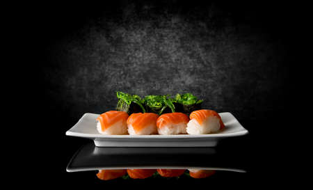 Sushi in plate on a black background