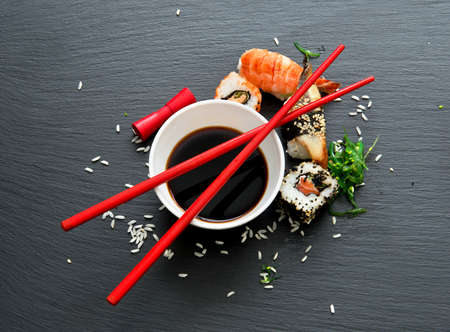 saucers: Sushi with soy in saucers on a slate table