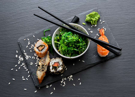sushi restaurant: Sushi and seaweed salad on slate table Stock Photo