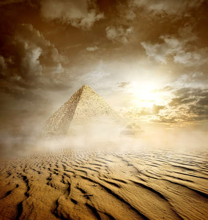 Storm clouds and pyramids in sand desert