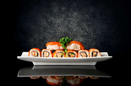 comida japonesa: Sushi y rollos en placa sobre un fondo negro