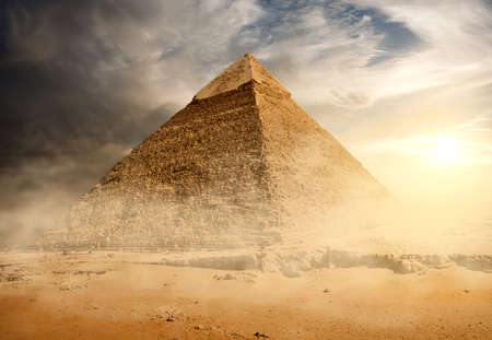 Pyramid in sand dust under gray clouds Stock Photo