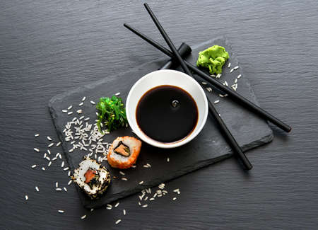 Rolls with sauce and chopsticks on a slate table