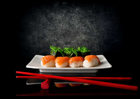 Sushi on plate with red chopsticks on black background Stockfoto