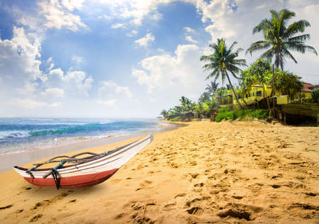 Small boat on a beach of the ocean in Sri Lanka
