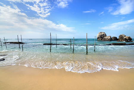 southern sri lanka: Wooden poles for fishing on a beach of indian ocean in Sri Lanka Stock Photo