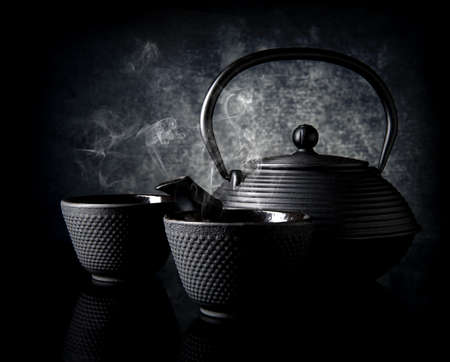 cast iron: Black teapot with small cups on black background Stock Photo