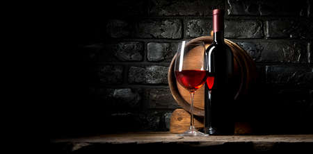 Red wine on a background of old black bricks Imagens