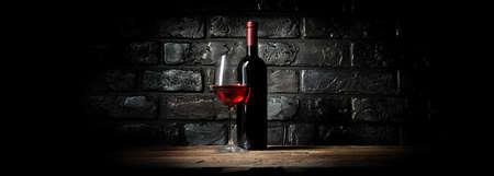 La botella y el vaso de vino cerca de la pared negro Foto de archivo