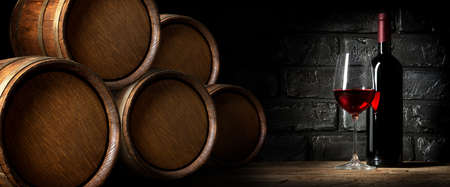 Red wine near barrels in cellar of winery Foto de archivo