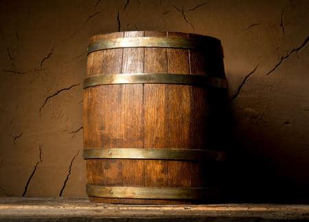 Wooden cask near clay wall in cellar