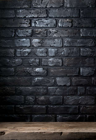 stone floor: Black brick wall and old wooden table Stock Photo