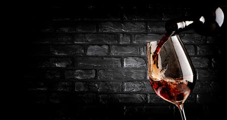 Wine pouring in wineglass near brick wall