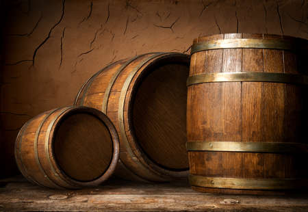 Three wooden barrels near clay wall in cellar
