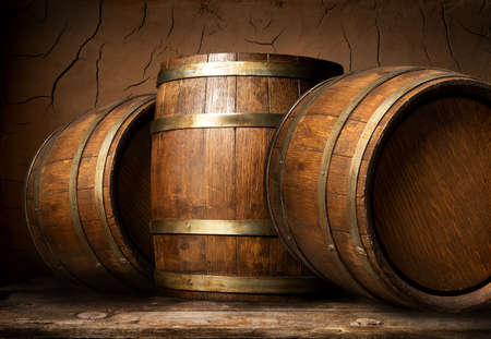 Old wooden barrels in cellar with clay wall Stockfoto