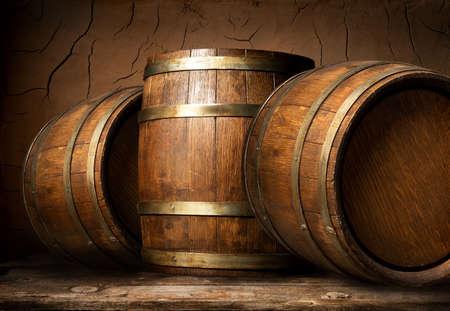 Viejos barriles de madera en bodega con pared de arcilla
