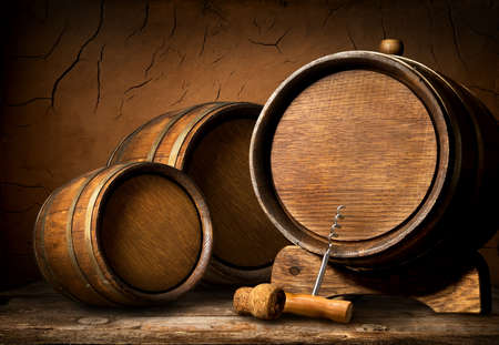 Wooden barrels and corkscrew in clay cellar