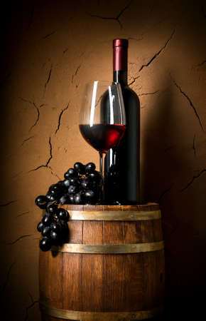 Wine on barrel in cellar with clay wall Stock Photo