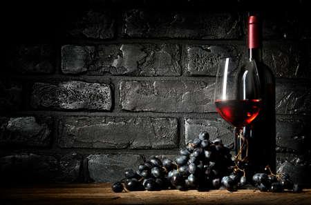 ブドウの束し、黒煉瓦背景上のワイン 写真素材