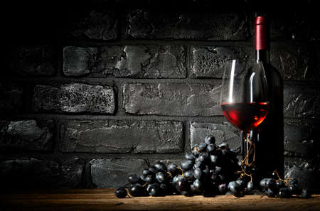 Bunch of grapes and wine on a black brick background Imagens