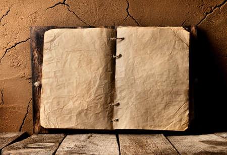Otwarta stara książka na stole przy ścianie gliny