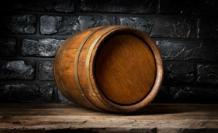 Brick wall and wooden barrel in cellar Stock Photo