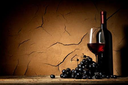 Ripe grape and wine near clay wall in cellar