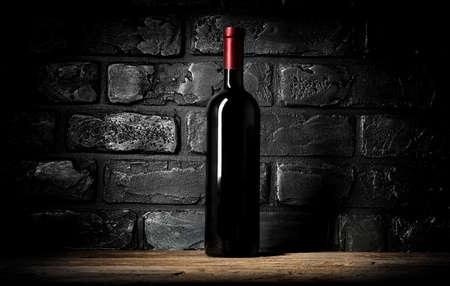 wine background: Bottle of wine near wall of black bricks