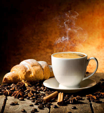 Fresh croissant and coffee with spices on table