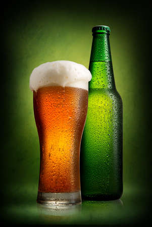 tall glass: Beer in bottle and tall glass on a green background