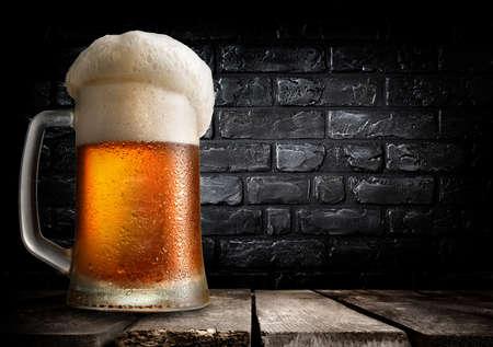 Mug of beer on table near black brick wall