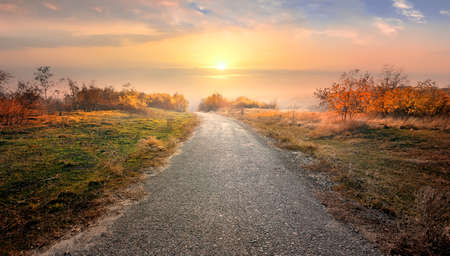 sunset clouds: Asphalted road through countryside in red autumn Stock Photo