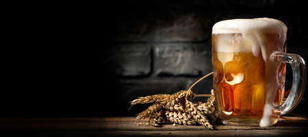 Beer in mug on wooden table near brick wall Stockfoto