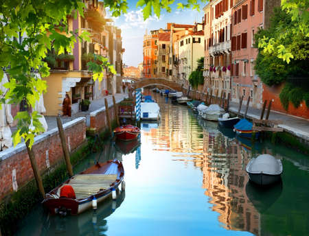 Boats in narrow venetian water canal, Italy