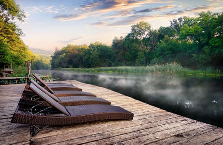 Chaise longues near river Stock Photo