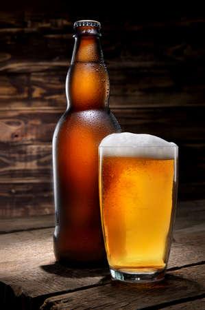 A bottle and a glass of beer on a wooden table background 写真素材